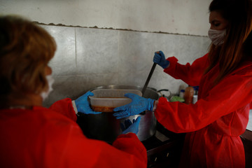 Volunteers wearing face masks serve stew in a plastic container for the low-income people at a soup kitchen during the spread of the coronavirus disease (COVID-19), in Florencio Varela, in the outskirts of Buenos Aires