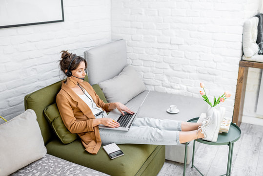 Young business woman working on computer, talking online using a headset while sitting on the comfortable sofa at home. Concept of remote work from home