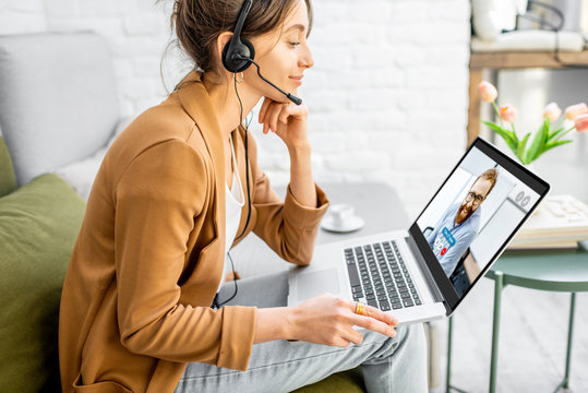 Business woman having a video call with coworker, working online from home at cozy atmosphere. Concept of remote work from home
