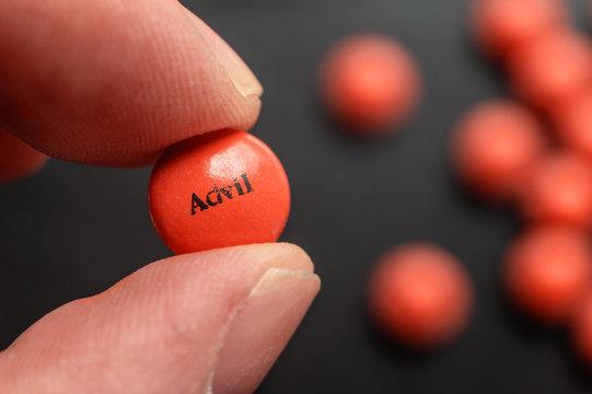 Fingers holding an Advil Ibuprofen tablet