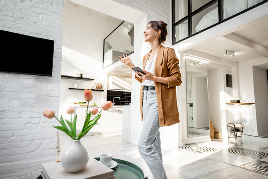 Woman having some business work, standing with a smart phone in the modern living room at cozy home. Concept of remote work from home
