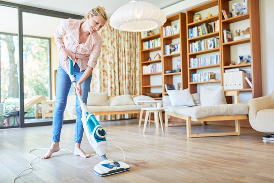 Woman cleans floor with steam cleaner
