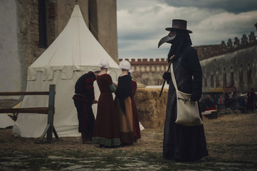A masquerade historical scene reconstruction. Plague doctor in medieval old town. Castle and epidemic