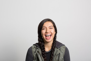 Studio portrait of a young woman laughing