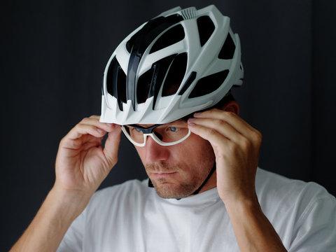 Close-up Portrait shot,  biker putting on a glasses and adjusting. Gray background..
