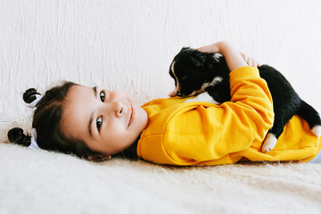 Side view indoor image of a smiling happy child playing at home with a little dog. Pretty little girl cares about the puppy. Adorable kid playing with her pet at the carpet in the room on a sunny day.