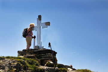 Frau an einem Gipfelkreuz in den Alpen