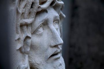 Fototapete - Ancient statue of Jesus Christ in profile against dark background. Religion, faith, death God concept.