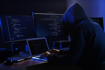 Hacker with computers in dark room. Cyber crime