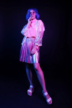 Fashionable young woman in neon light in full growth in a nightclub. The girl is wearing a wig, glasses and a shiny, halo jacket and skirt.