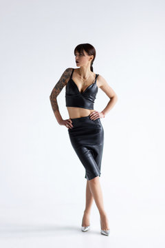 Beautiful young woman wearing leather top and skirt