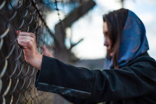 The migrant is holding his hands behind the protective fence
