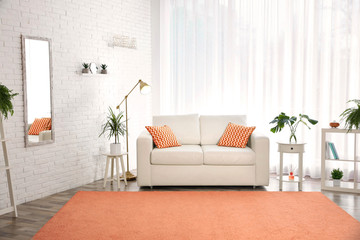 Stylish room interior with comfortable sofa and orange carpet