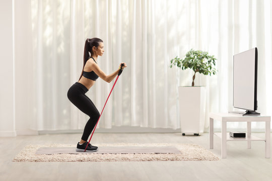 Young woman in sportswear exercising with a resistance band in front of a tv