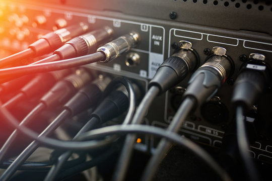 Close up audio jacks cable plugged into mixer console. XLR audio cable