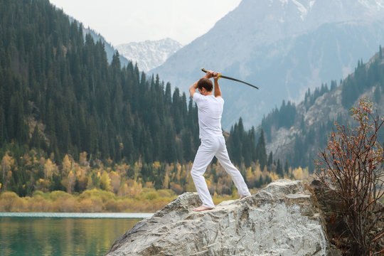 A man holds a Japanese sword katana above his head. Training combat skills.