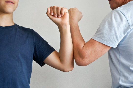 Man and youngster shaeking elbows instead of hand shake as greetings