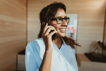 Woman in office talking on phone and smiling Fotomurales