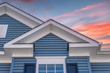 Triangle shape decorative gable with colonial white soffit and fascia on a blue horizontal vinyl siding modern American estate home with colorful dramatic stunning orange sunset sky