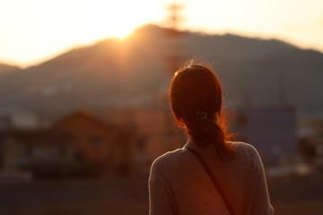 夕陽を眺める女性
