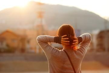 夕陽と女性の後ろ姿