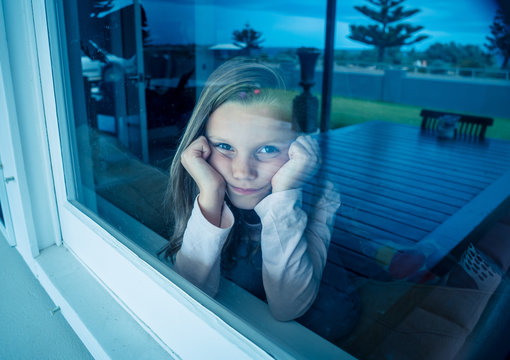 COVID-19 Quarantine. Sad little girl looking through the window feeling lonely during lockdown