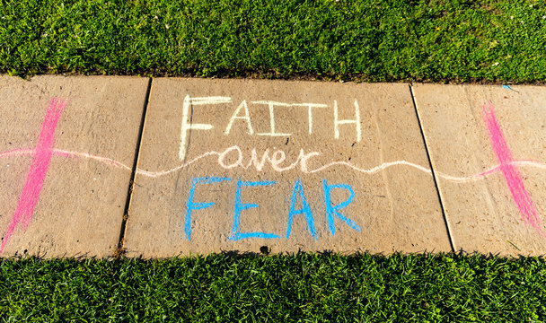 "The phrase ""Faith over Fear"" written with sidewalk chalk on gray concrete pavement background."
