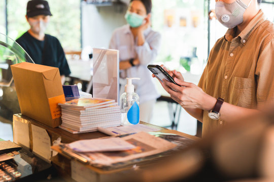 Women in protective face mask placing an order with cell phone at cafe counter.