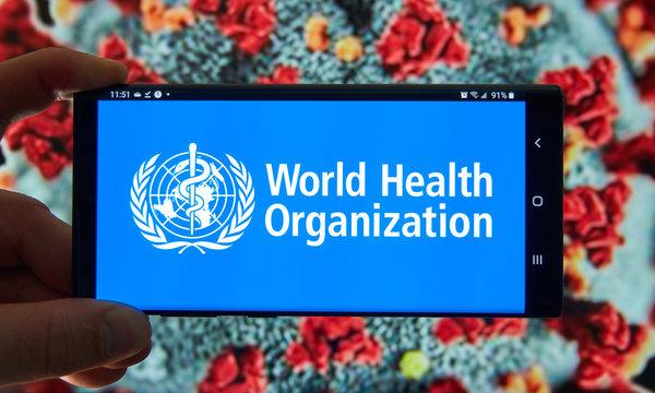 The World Health Organization logo on mobile screen over coronavirus background.