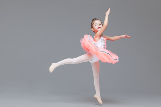 Cute adorable ballerina little girl in pink tutu dance practices ballet dancing
