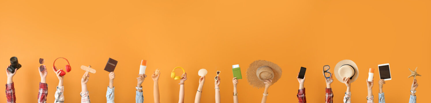 Many hands with travel items on color background