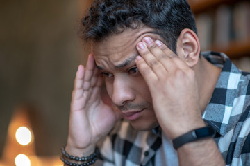 Dark-haired man in a checkered shirt having a headache