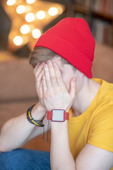 Young man in a red hat sitting with his face closed