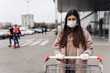 Young woman wearing protection face mask against coronavirus 2019-nCoV pushing a shopping cart.