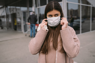 Woman puts on a protective medical mask.