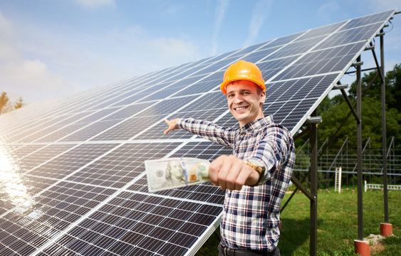 Smiling guy with hundred dollar bill in hand shows at station of solar panels in which the sun's rays are reflected. Business and generation concept. Green ecological power energy generation.