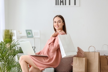 Young woman with shopping bags at home