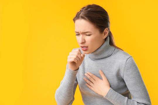 Ill coughing young woman on color background