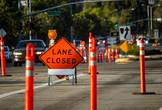 Traffic sign in diamond shape stating Lane Closed with traffic barrier stantions in foregound and background