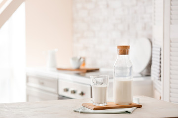 Glass and bottle of fresh milk on table