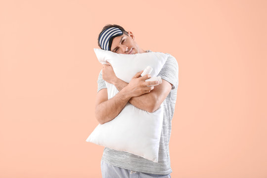 Young man with sleeping pills and pillow on color background