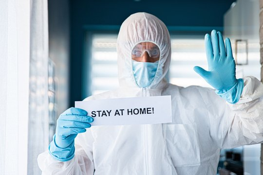 Man in protective anti virus suit and mask holding card with message stay at home