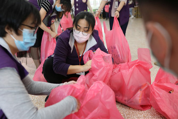 Taoyuan health department staffers pack 300 sets of care packages, to be delivered to people who have been ordered to be under self-quarantine, in Taoyuan