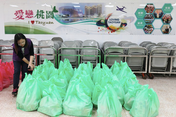 A Taoyuan health department staffer packs 300 sets of care packages, to be delivered to people who have been ordered to be under self-quarantine, in Taoyuan