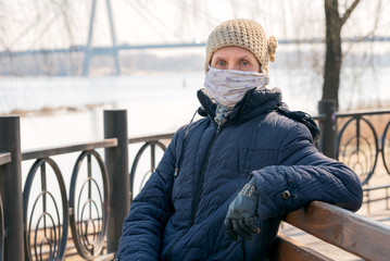 A poor elderly woman wears a homemade mask to protect herself from viruses such as coronavirus, also known as covid-19, or SARS and MERS. She sits on a bench close to the river