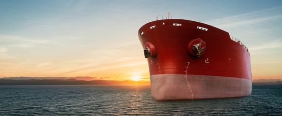 Close up of large red merchant crago ship in the ocean underway. at sunrise or sunset .Performing cargo export and import operations.