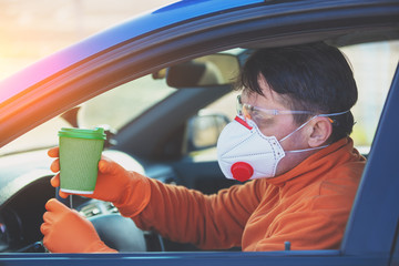 A man in medical face mask and safety glasses during an epidemic in the car