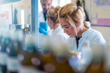 Beautiful young woman scientist in laboratory working. Young female scientist doing some research.