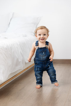 Smiling baby making first steps in bedroom