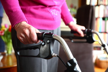hands of an elderly lady resting on the handles of her walker